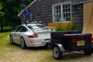 Expensive car with trailer and bike on roof
