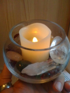 A small glass bowl filled with coloured crystals and glass surrounding a candle
