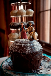 Chocolate wedding cake in foreground with king and queen figures on top, a large rack of homemade muffins in the background