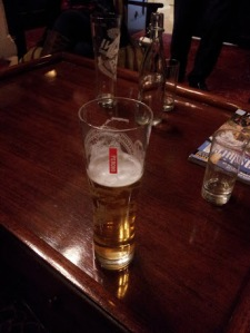 half a pint of lager on a mahogany table