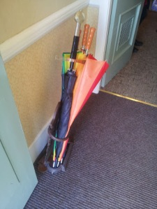 A sword hilted umbrella in an umbrella stand
