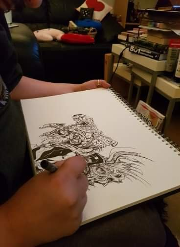 Picture of intricate inkpen artwork taken over the artist's shoulder, showing the page, his arm, and fine pen