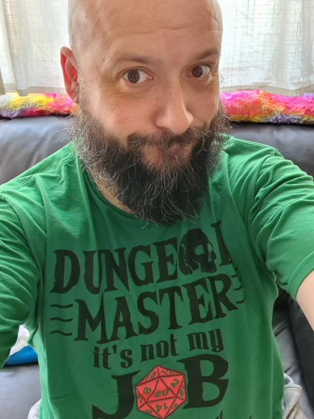 Tim wearing a green tshirt with the caption: Dungeon Master - It's not my job to kill you, it's just one of the perks